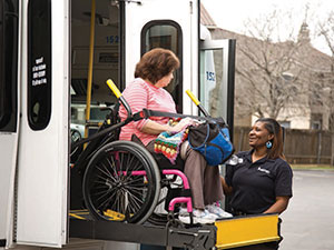 section8-MetroAccess-customer-in-a-wheelchair-boarding-a-MetroAccess-bus-via-a-lift-assisted-by-the-MetroAccess-vehicle-operator