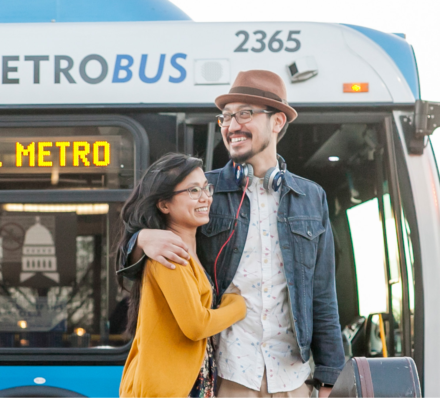 Image of a Happy Couple standing in front of a Capital Metro Bus