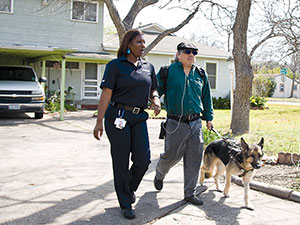 MetroAccess customer with service animal being escorted down a driveway by a MetroAccess vehicle operator